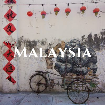 """""""Malaysia"""" written across a photo of a peeling street mural of a man loading sacks onto a bicycle, below a strand of red lanterns."""