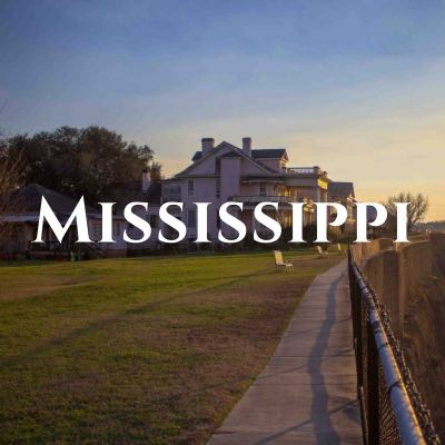 """""""Mississippi"""" written across a photo of a concrete path and grassy area in front of a mansion."""