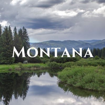 """""""Montana"""" written across a photo of hills and pine trees above their reflection in water."""