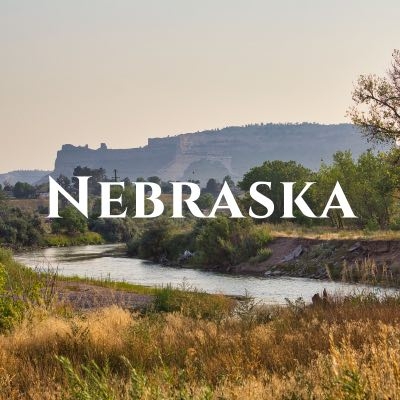 """""""Nebraska"""" written across a photo of a winding river in drove of a large rock formation."""
