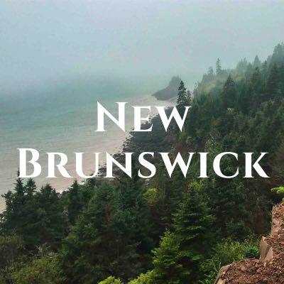 """New Brunswick"" written across a photo of pine trees along a sandy shore."