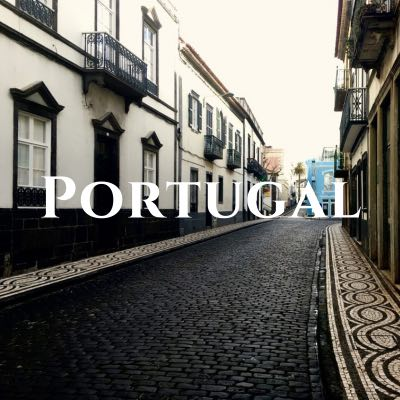 """""""Portugal"""" written across a photo of a narrow brick street lined with off-white buildings."""