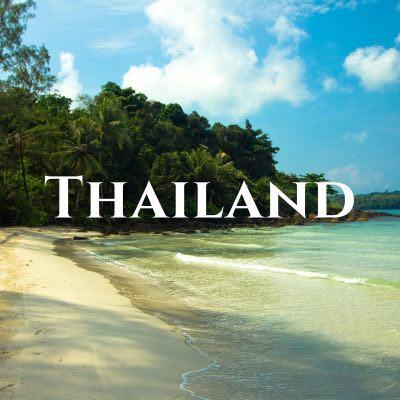 """Thailand"" written across a photo looking down a sandy beach toward thick palm trees."