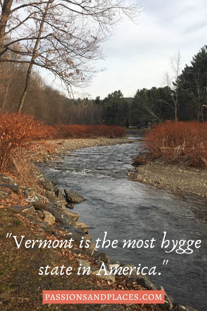 """Narrow river lined with red bushes, behind the quote, """"Vermont is the most higgle state in America."""""""