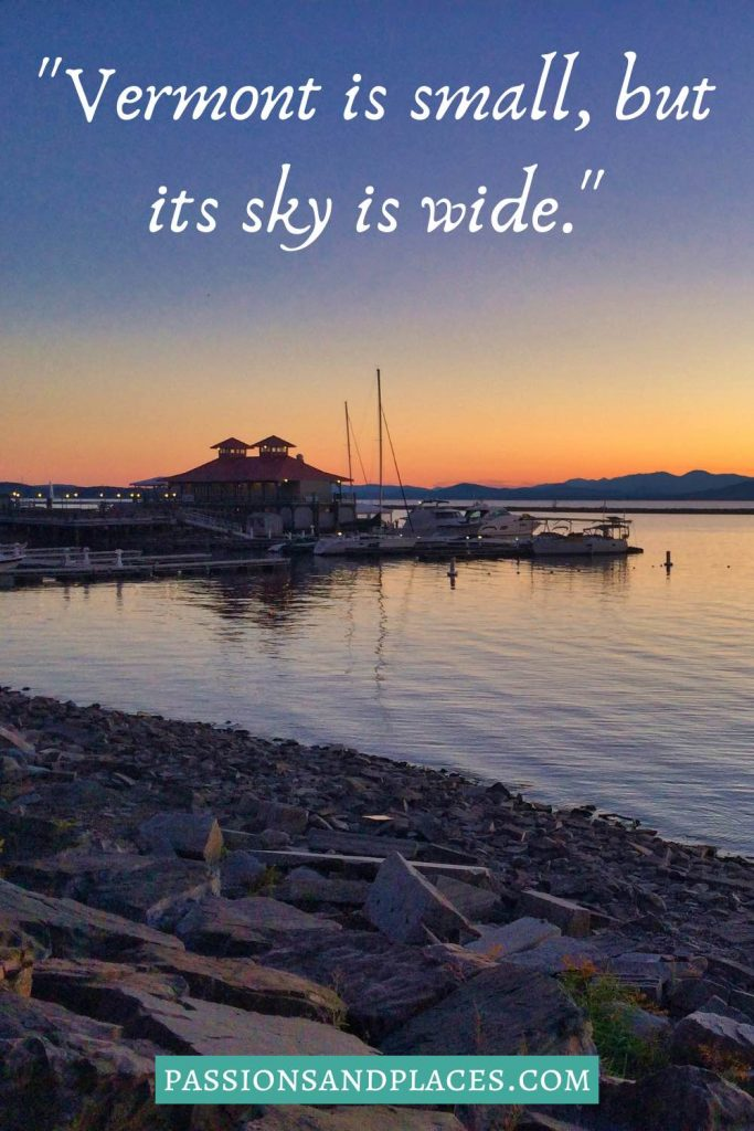 """Building and boats on the water at sunset, behind the quote, """"Vermont is small, but its sky is wide."""""""