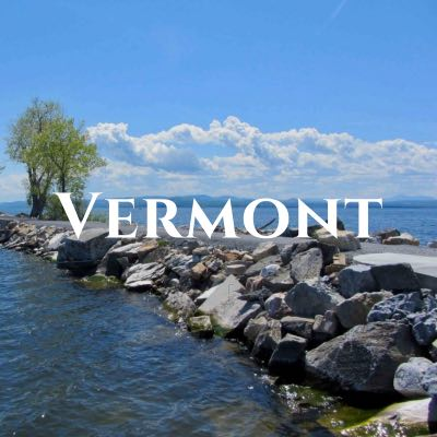 """""""Vermont"""" written across a photo of a rocky path stretching across open water."""