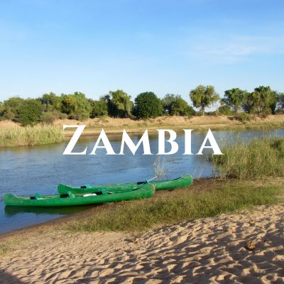"""Zambia"" written across a photo of two green kayaks sitting on a sandy riverbank."
